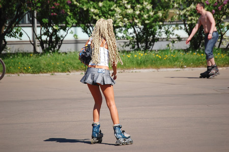 Girl with long hair and short skirt on roller rides on the green summer park.