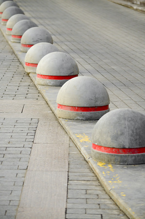 kerb: Round stone road kerb with a red strip standing in a row and on a diagonal on a paving stone. Stock Photo
