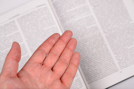 male palm: The male palm shows on the big open book with text.
