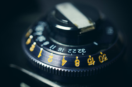 macro film: Old film DSLR camera. The dial sensitivity of the film. Rewinding the film. Close up view. Macro. Selective focus. Vintage photo. Toning.
