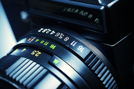 macro film: Old film DSLR camera with lens. The scale of the aperture, depth of field and distance. Close up view. Macro. Selective focus. Vintage photo. Toning.