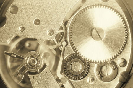 recurrence: Gears old mechanical watches. Pendulum, cogs under the hood. Close up view, selective focus. Vintage toning. Morning fog glow.