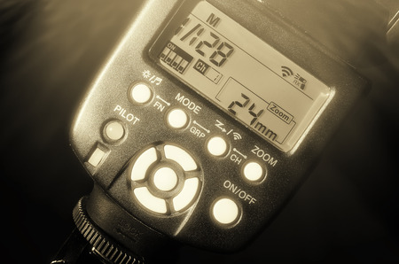 pilot light: The rear part of the electronic system flash for camera. LED with numbers and symbols, white buttons control functions. Black and white photo. Low key.