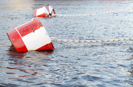 buoys: Red and white metal mooring buoys. Stock Photo