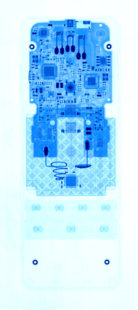 under control: TV remote control under X-rays in blue tones on white background. Visibility through. Image was obtained with real X-ray machine.
