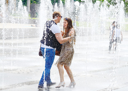 MOSCOW, RUSSIA - May 30, 2016: Unknown woman and man bathing city fountain. Hot summer heat. Girls wet dress. Wet long hair. Bright emotions face. Icy freshness, happiness.Street stories.Love, romance Editorial