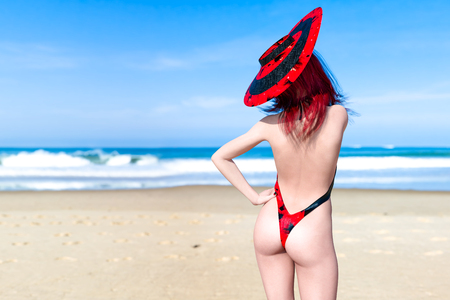 3D Beautiful woman in black swimsuit and hat on sea beach. Summer rest. Blue ocean background. Sunny day. Conceptual fashion art. Seductive candid pose. Realistic render illustration.