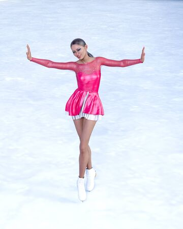 Young beautiful girl ice skating.Figure skater athlete woman short red dress.Demonstration performance on ice.Bright make up.Conceptual fashion art.3D render illustration. Banque d'images