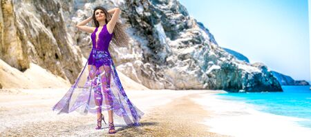 3D beautiful woman light transparent summer purple dress sea beach.Rocky coast clear white sand.Summer rest.Blue ocean background.Sunny day.Conceptual fashion art.Seductive pose.Render illustration.