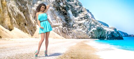 3D render beautiful woman light Aqua Menthe dress sea beach.Rocky coast clear white sand.Summer rest.Blue ocean background.Sunny day.Conceptual fashion art.color trend of the year