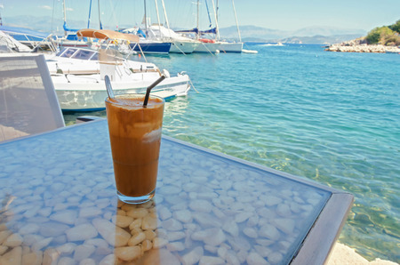 sweet shop: ice coffee on a table with a view of the sea and harbor Stock Photo