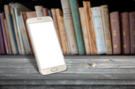 android: Smart phone on table in library Stock Photo