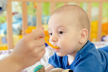 cute baby boy: baby boy eating on the bed