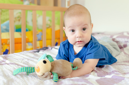 cute animals: baby boy playing with soft toy on the bed