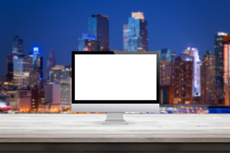 computer monitor: computer monitor on wooden desk city sky line lights in the background display mock up Stock Photo