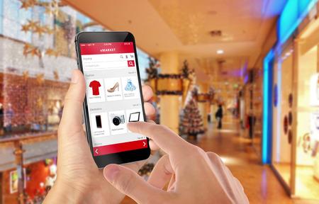 크리스마스 도중 손에 스마트 전화 온라인 쇼핑. 백그라운드에서 쇼핑 센터입니다. 전자 상거래 웹 사이트로 의류 신발 액세서리 구입 스톡 콘텐츠