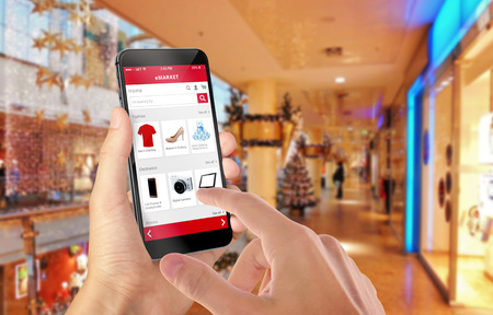 e commerce: Smart phone online shopping in man hand during Christmas. Shopping center in background. Buy clothes shoes accessories with e commerce web site Stock Photo