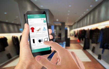 e commerce: Smart phone online shopping in man hand. Shopping center in background. Buy clothes shoes accessories with e commerce web site