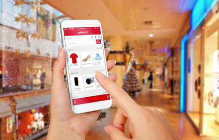 buy online: Smart phone online shopping in woman hand during Christmas. Shopping center in background. Buy clothes shoes accessories with e commerce web site