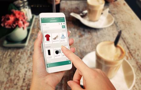여자 손에 스마트 폰 온라인 쇼핑. 배경 CAFFE와 책상. 전자 상거래 웹 사이트와 옷을 신발 액세서리를 구입
