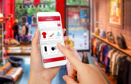 Smart phone online shopping in woman hand. Shopping center in background. Buy clothes shoes accessories with e commerce web site Foto de archivo