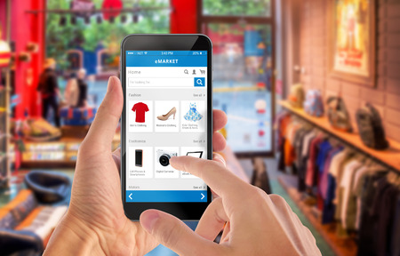 スマートな男の手で携帯電話のオンライン ショッピングします。バック グラウンドでのショッピング センターです。服靴アクセサリー e コマース w 写真素材