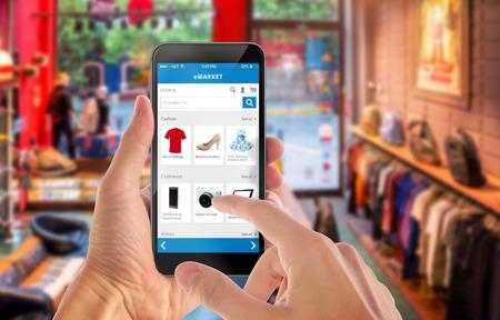 Smart phone achats en ligne en main de l'homme. Centre commercial en arrière-plan. Acheter des vêtements chaussures accessoires avec e-commerce site web