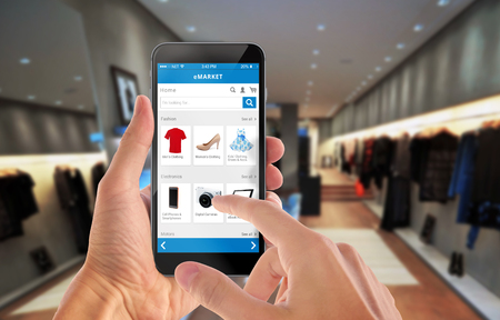 buy online: Smart phone online shopping in man hand. Shopping center in background. Buy clothes shoes accessories with e commerce web site