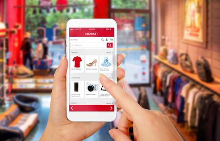 tienda de zapatos: Teléfono inteligente compras en línea en mano de la mujer. Centro comercial en el fondo. Comprar ropa calzado accesorios con el correo web de comercio Foto de archivo