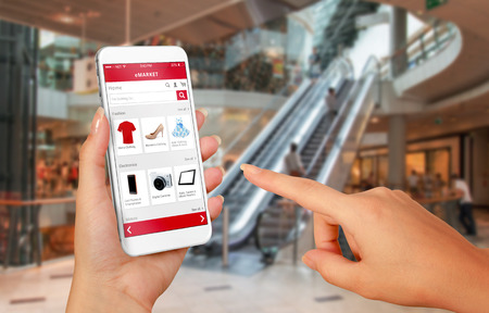 Smart phone online shopping in woman hand. Shopping center in background. Buy clothes shoes accessories with e commerce web site 스톡 콘텐츠
