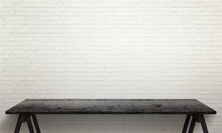 Black wooden table with legs. White brick wall texture in background.