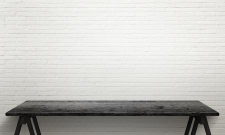 Zwarte houten tafel met de benen. Witte bakstenen muur textuur in de achtergrond.