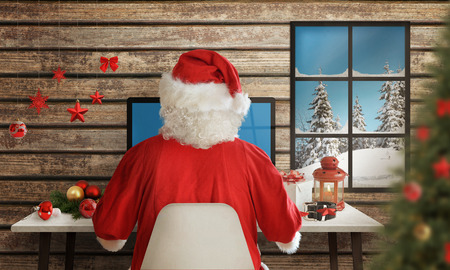 glass office: Santa Claus responds to letters on a computer for Christmas Stock Photo