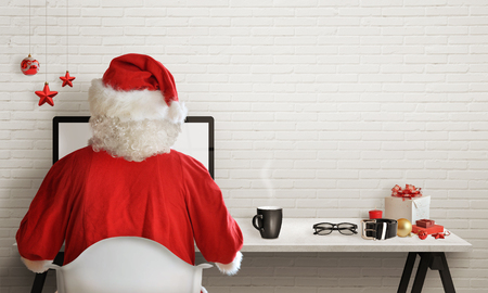 Santa Claus responds to letters on a computer for Christmas 스톡 콘텐츠