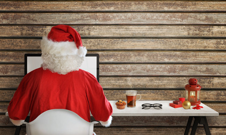 santa suit: Santa Claus responds to letters on a computer for Christmas Stock Photo