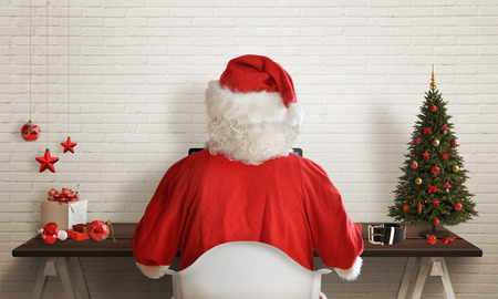responds: Santa Claus responds to letters on a computer for Christmas Stock Photo