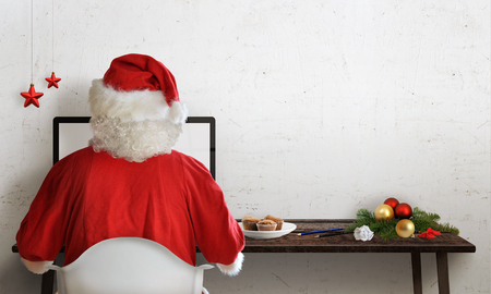 man hat: Santa Claus responds to letters on a computer for Christmas Stock Photo
