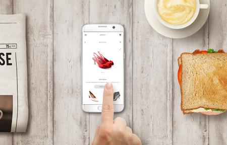 Online-Shopping mit Smartphone. Kaufende Frauenschuhe auf Online-Shop mit der Hand. Entspannen Sie sich mit Saft. Standard-Bild - 55855833