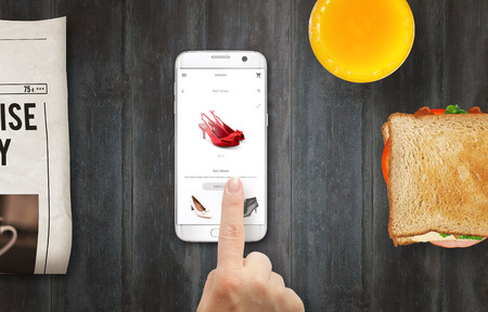 buying time: Online shopping with smart phone. Buying women shoes on online store with hand. Relax time with coffee, sandwich, newspaper on table.