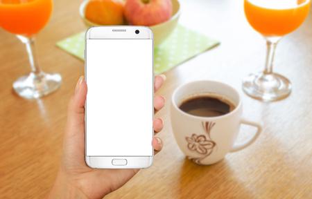 持つスマート フォンは手にモックアップの表示を分離しました。テーブルの上のコーヒーを飲みながら時間をおくつろぎください。 写真素材