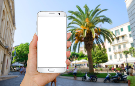 vocation: Smart phone in woman hand with isolated white display for mockup. Street with palm in background. Summer, vocation time in mediterranean city.