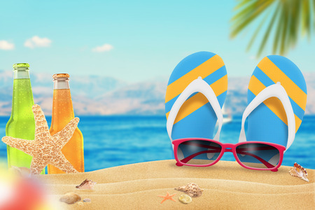 Sunglasses, juice and slippers on beach. Starfish and shells on sand. Beach and sea with palm in background. Stock Photo