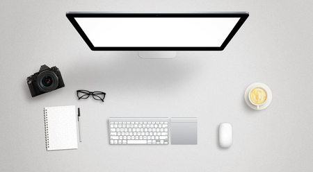 Isolated computer display for mockup on work desk with keyboard, mouse, coffee, camera, notebook, glasses, pencil. Stock Photo