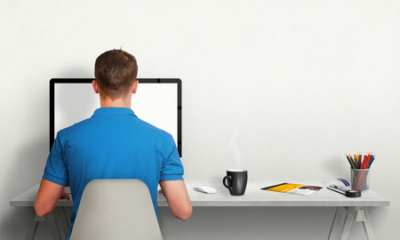 Man working on computer with isolated screen in office interior. Work desk with keyboard, mouse, cup of coffee, paper, pencils. Free space on wall for text.