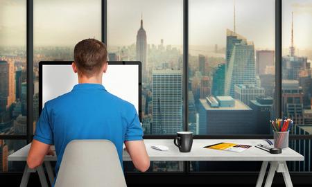 街や高層ビルを見下ろすオフィス インテリアの分離の画面のコンピューターで作業する男性。キーボード、マウス、コーヒー、紙、鉛筆のカップ付