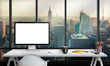 Isolated computer display for mockup in office interior overlooking the city and skyscrapers. Work desk with keyboard, mouse, cup of coffee, paper, pencils. Stock Photo