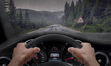 Driving in rainy weather. View from the driver angle while hands on the wheel. Alongside the road is a sign for slippery road. Rain splashed windshield. Imagens