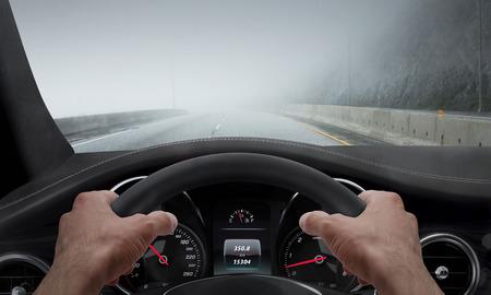 안개 낀 날씨에 운전. 바퀴에 손을 운전하는 동안 운전자 각도에서 봅니다.