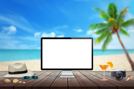 palm computer: Isolated computer display on wooden table for mockup. Cocktail, camera, hat, shells, stones, sunglasses on table. Beach, sea, palm and blue sky in background. Stock Photo