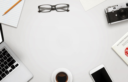 本文の空き領域のオフィス デスク。ノート パソコン、スマート フォン、カメラ、メガネ、一杯のコーヒー、紙、本、メモ帳、鉛筆白い木製のテー
